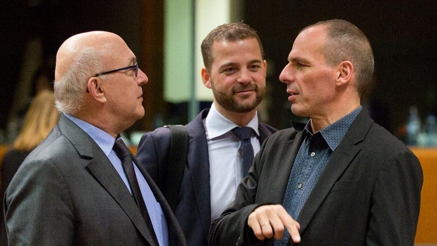 Greek Finance Minister Yanis Varoufakis, right, speaks with French Finance Minister Michel Sapin, left, during a meeting of EU finance ministers at the EU Council building in Brussels on Tuesday, March 10, 2015. Ministers on Tuesday will discuss the EU's banking union, the European semester and strategic investment. (AP Photo/Virginia Mayo)