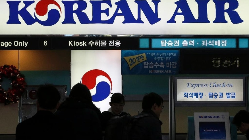 In this Dec. 16, 2014 photo, passengers wait to check in at the domestic check-in desk of Korean Air Lines Co. at Gimpo Airport in Seoul, South Korea. A flight attendant who was harassed by a former Korean Air Lines Co. vice president in what became known as the nut rage case filed a civil lawsuit against the airline and the executive. (AP Photo/Lee Jin-man)