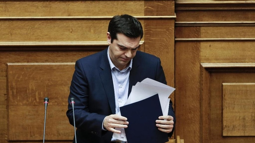 Greece's Prime Minister Alexis Tsipras arranges his papers after his speech at a parliament session in Athens, on Tuesday, March 10, 2015. Tsipras spoke during a special debate on whether to revive a parliamentary committee that would seek German World War II reparations that Greece says were never fully paid. The committee would also seek the return of a forced loan raised by Nazi occupation forces, and of Greek antiquities removed during the war.(AP Photo/Petros Giannakouris)
