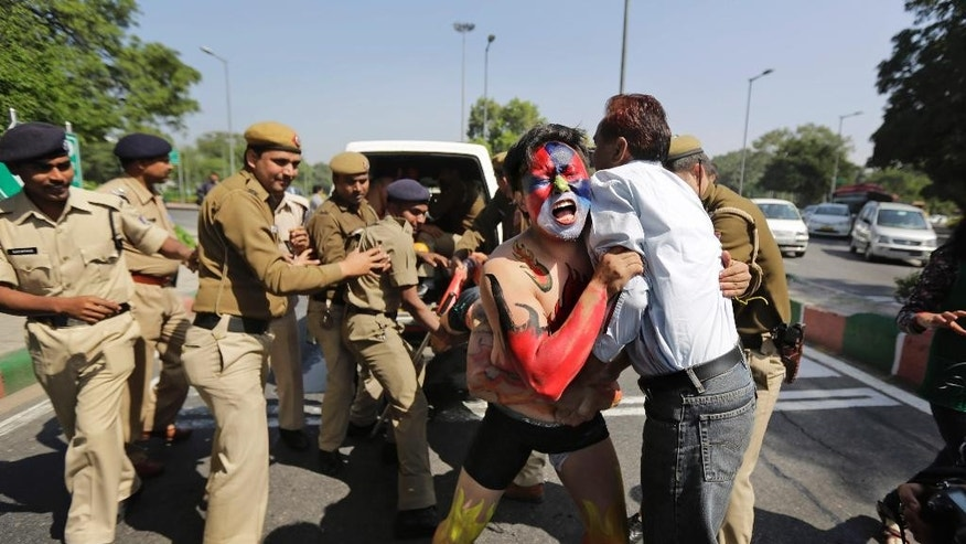 Indian policemen detain a Tibetan exile, his face painted in the colors of the Tibetan flag, during a protest in New Delhi, India, Tuesday, March 10, 2015. Indian police on Tuesday detained about 100 Tibetans who were protesting outside the Chinese Embassy in New Delhi on the anniversary of a failed 1959 uprising against China's rule in Tibet. The protest was to mark the 56th anniversary of the uprising, which led to the flight of the Dalai Lama, the Tibetans' spiritual leader, and the establishment of the Tibetan government-in-exile in a north Indian town. (AP Photo/Altaf Qadri)