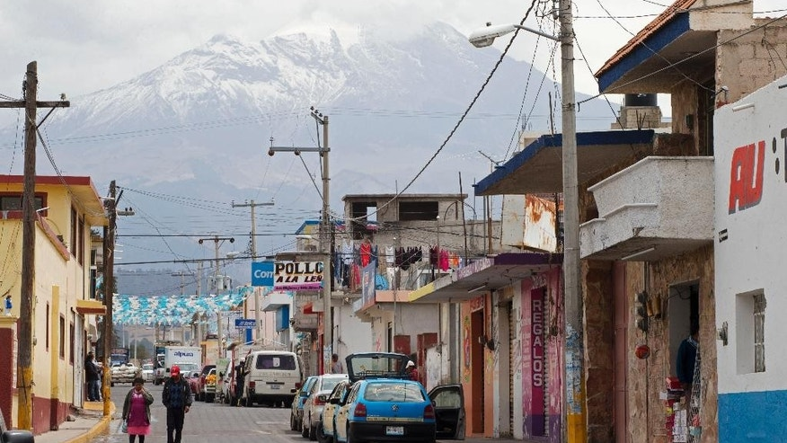 The Pico de Orizaba volcano rises above the town of Tlachichuca in Mexico's Puebla state, Tuesday, March 10, 2015. Retired mountaineer Luis Espinosa, 78, a survivor of a 1959 expedition in which one climber died and three disappeared in an avalanche, is convinced that two mummified bodies discovered last week in a glacier on Mexico's tallest peak are the remains of his missing fellow climbers. (AP Photo/Rebecca Blackwell)