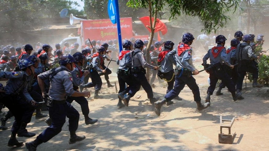 Myanmar police with batons rush towards protesters to charge them in Letpadan, 140 kilometers (90 miles) north of Yangon, Myanmar, Tuesday March 10, 2015. Hundreds of police were charging student protesters with batons, kicking and beating them as they drag them into trucks, ending a days-long standoff in the Myanmar town of Letpadan. Witnesses say many of the demonstrators were injured in Tuesday's crackdown, though it was not clear how badly. (AP Photo/Khin Maung Win)
