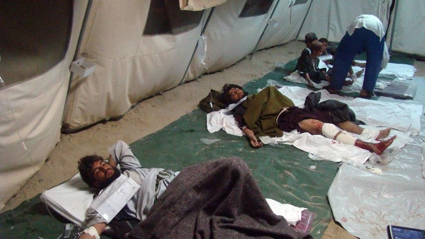 Wounded Afghani men and children lie on the ground in a tent after a deadly attack targeted a checkpoint, in Lashkar Gah, capital of the southern Helmand province, Afghanistan, Tuesday, March 10, 2015. A series of bombings across Afghanistan killed at least 13 people and wounded dozens Tuesday, authorities said. Afghanistan's army has been fighting to clear large parts of Helmand of Taliban militants. (AP Photo/Abdul Khaliq)