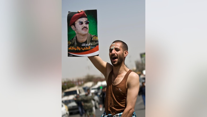 A Yemeni man holds a poster of Ahmed Ali Abdullah Saleh, the son of Yemeni former President Ali Abdullah Saleh, and chants slogans during a demonstration demanding presidential elections be held and the younger Saleh run for the office, in Sanaa, Yemen, Tuesday, March 10, 2015. (AP Photo/Hani Mohammed)