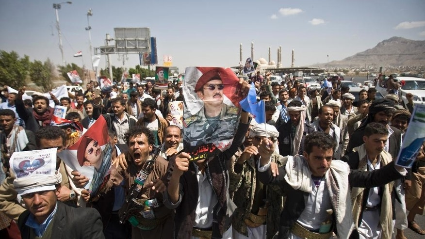 Supporters of Ahmed Ali Abdullah Saleh, the son of Yemeni former President Ali Abdullah Saleh, wave banners and shout slogans during a demonstration demanding presidential elections be held and the younger Saleh run for the office, in Sanaa, Yemen, Tuesday, March 10, 2015. (AP Photo/Hani Mohammed)