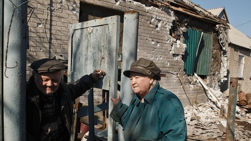 "An elderly couple stand in front of their badly damaged house in Debaltseve, Ukraine, Monday, March 9, 2015. More than 6,000 people have died in eastern Ukraine since the start of the conflict almost a year ago that has led to a ""merciless devastation of civilian lives and infrastructure,"" according to the U.N. human rights office. (AP Photo/Vadim Ghirda)"
