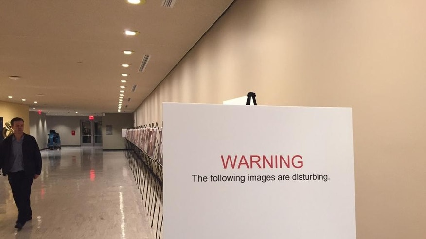 The sign warns of disturbing images as a man walks past a photo exhibit at United Nations headquarters, Tuesday, March 10, 2015. The graphic photo exhibit shows detainees who have died in Bashar Assad's prisons since the start of Syria's conflict. (AP Photo/Cara Anna)