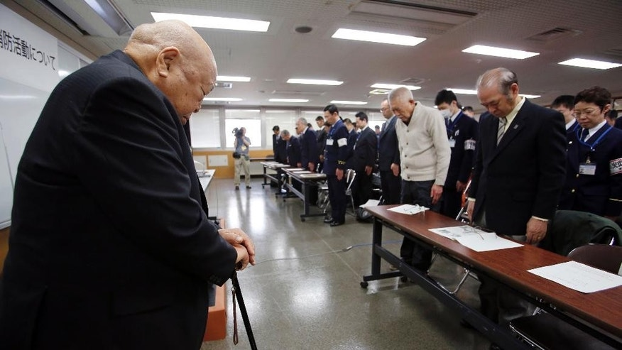 In this March 5, 2015 photo, former firefighter Isamu Kase, left, and firefighters offer silent prayers for the victims of March 10, 1945, firebombing of Tokyo, in a lecture at Joto fire department in Tokyo. Kase survived the firebombing. Japan mourned Tuesday for the 105,400 people killed in a single night 70 years ago, when U.S. B-29 bombers obliterated much of Tokyo in the deadliest conventional bomb attack ever. (AP Photo/Shizuo Kambayashi)