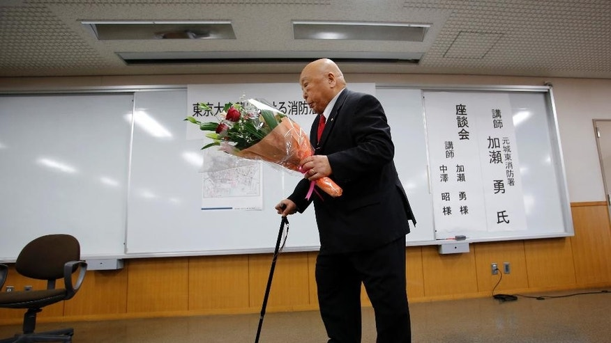 In this March 5, 2015 photo, former firefighter Isamu Kase holds a bouquet after a lecture at Joto fire department in Tokyo. Kase survived the March 10, 1945, firebombing of Tokyo. Japan mourned Tuesday for the 105,400 people killed in a single night 70 years ago, when U.S. B-29 bombers obliterated much of Tokyo in the deadliest conventional bomb attack ever. (AP Photo/Shizuo Kambayashi)
