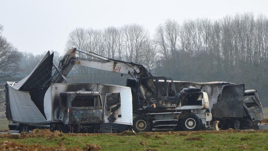 Burnt out vans stand near the Avallon motorway exit, central France, Wednesday, March 11, 2015. A police official says 15 armed assailants attacked two vans on a French highway carrying millions of euros worth of jewels, and sped away. The official says the two vans were found burned in a forest near the site of the attack, which happened on the A6 highway connecting Paris and Lyon. The jewels were not found. (AP Photo)