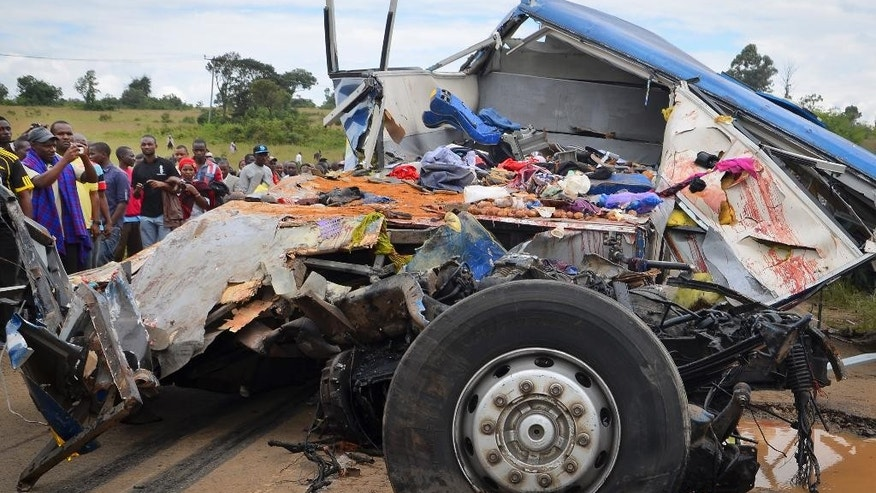The remains of passenger's belongings lie in the blood-streaked wreckage at the scene of a bus crash near Changarawe village in the Mafinga District of the Iringa region of Tanzania Wednesday, March 11, 2015. A Tanzanian police official says dozens of people were killed when a truck carrying a shipping container rammed into the bus. (AP Photo)