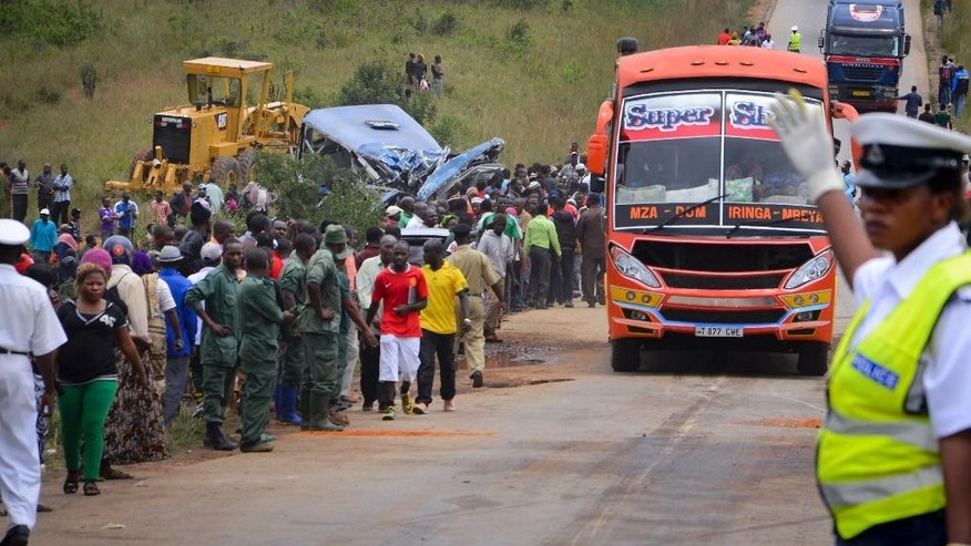 A police officer keeps traffic and people away from the scene of a bus crash, center-left, near Changarawe village in the Mafinga District of the Iringa region of Tanzania, Wednesday, March 11, 2015. A Tanzanian police official says dozens of people were killed when a truck carrying a shipping container rammed into the bus. (AP Photo)