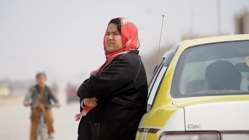 In this Tuesday, March 3, 2015 photo, Afghan taxi driver, Sara Bahai, 40, right, waits for customers in Mazar-i Sharif city, capital of northern Balkh province, Afghanistan. For Bahai, becoming Afghanistan's first and only woman taxi driver in living memory was a pragmatic step rather than a brave one. But in a country where women are regarded as inferior to men and often suffer horrific abuse simply because of their sex, she has also become a breadwinner, trailblazer and role model who believes women must stand up for themselves if her country is to achieve peace, prosperity and happiness. (AP Photo/Mustafa Najafizada)