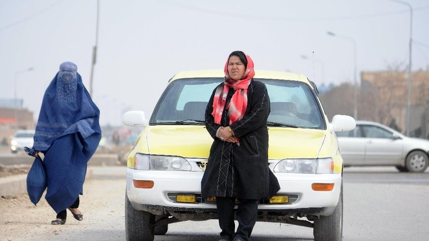 In this Tuesday, March 3, 2015 photo, taxi driver Sara Bahai, 40, right, waits for customers in Mazar-i Sharif city, capital of northern Balkh province, Afghanistan. For Bahai, becoming Afghanistan's first and only woman taxi driver in living memory was a pragmatic step rather than a brave one. But in a country where women are regarded as inferior to men and often suffer horrific abuse simply because of their sex, she has also become a breadwinner, trailblazer and role model who believes women must stand up for themselves if her country is to achieve peace, prosperity and happiness. (AP Photo/Mustafa Najafizada)