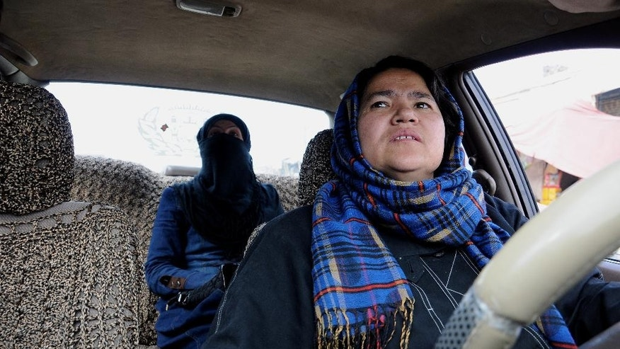 In this Tuesday, March 3, 2015 photo, taxi driver Sara Bahai, 40, right, drives a customer, in Mazar-i Sharif city, capital of northern Balkh province, Afghanistan. For Bahai, becoming Afghanistan's first and only woman taxi driver in living memory was a pragmatic step rather than a brave one. But in a country where women are regarded as inferior to men and often suffer horrific abuse simply because of their sex, she has also become a breadwinner, trailblazer and role model who believes women must stand up for themselves if her country is to achieve peace, prosperity and happiness. (AP Photo/Mustafa Najafizada)
