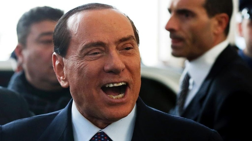 """FILE - In this Saturday, Dec. 29, 2012 file photo former Italian premier Silvio Berlusconi smiles as he arrives at Milan's central train station, Italy. Italy's highest court has upheld Silvio Berlusconi's acquittal in his notorious """"bunga bunga"""" case, giving the former premier a welcome victory as he tries to rally his Forza Italia party ahead of regional elections in May. (AP Photo/Luca Bruno)"""
