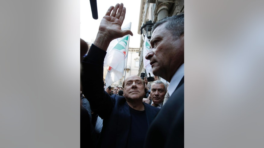 """Former Italian Premier Silvio Berlusconi, center, waves to supporters as he arrives at his residence of Palazzo Grazioli in Rome, Wednesday, March 11, 2015. Berlusconi savored his court victory in the infamous """"bunga-bunga"""" case Wednesday by plunging headfirst into politics, saying he's working for a better Italy even though he remains barred from public office. (AP Photo/Andrew Medichini)"""