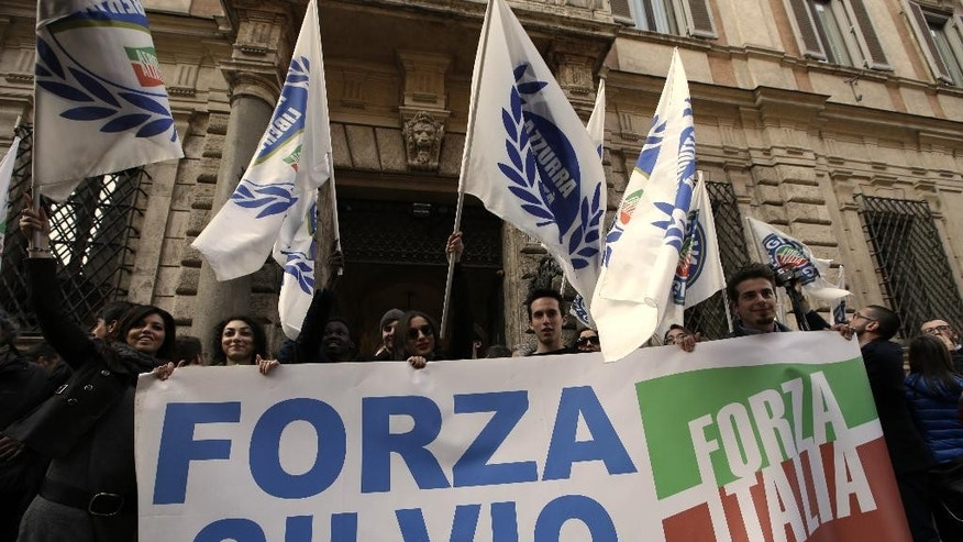 """Supporters of former Italian Premier Silvio Berlusconi expose a banner reading in Italian """"Go Silvio"""" in front of Palazzo Grazioli, the residence of Berlusconi, in Rome, Wednesday, March 11, 2015. Berlusconi savored his court victory in the infamous """"bunga-bunga"""" case Wednesday by plunging headfirst into politics, saying he's working for a better Italy even though he remains barred from public office. (AP Photo/Andrew Medichini)"""