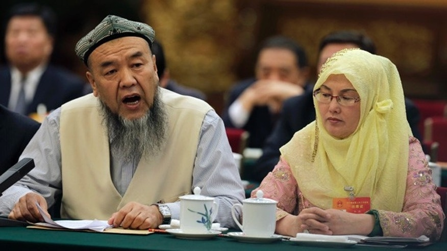 March 10, 2015: A delegate, left, from the Xinjiang Uyghur Autonomous Region speaks during the Xinjiang delegation group's meeting on the sideline of the National People's Congress in Beijing. (AP Photo/Andy Wong)