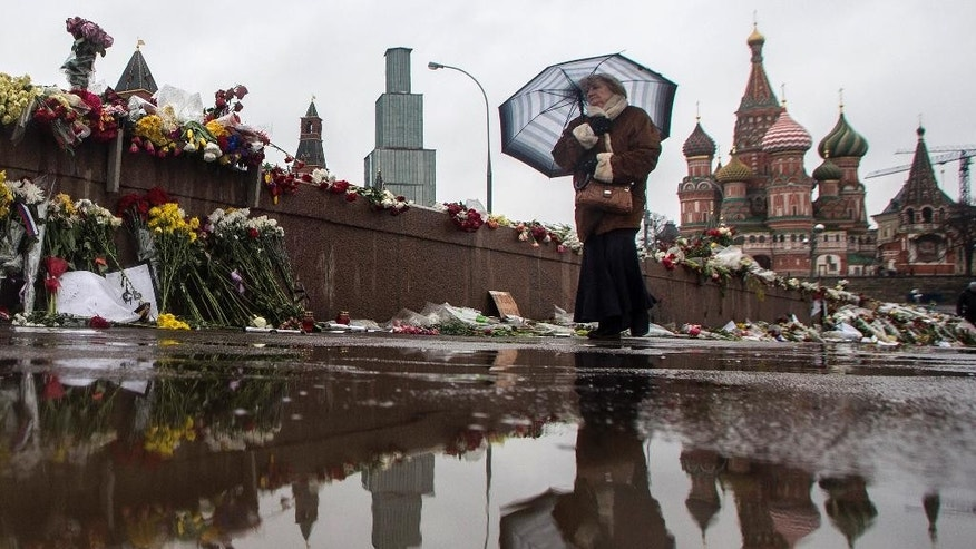 An elderly woman passes the place where Boris Nemtsov, a charismatic Russian opposition leader and sharp critic of President Vladimir Putin, was gunned down on Friday, Feb. 27, 2015 near the Kremlin, in Moscow, Russia, Sunday, March 8, 2015, with the Kremlin Wall and St. Basil's Cathedral are on the background. Russian news agencies said Sunday one of the suspects in the killing of Nemtsov has admitted involvement in the crime. Judge Nataliya Mushnikova said that Zaur Dadaev made a statement confirming his guilt, according to the reports. They did not specify his alleged actions. Dadaev is among five suspects detained in the Feb. 27 killing, when Nemtsov was shot while walking on a bridge near the Kremlin. Another man, Anzor Gubashev, was charged in the killing, and a hearing for three other suspects was under way, court spokeswoman Anna Fadeeva said earlier Sunday. (AP Photo/Denis Tyrin)