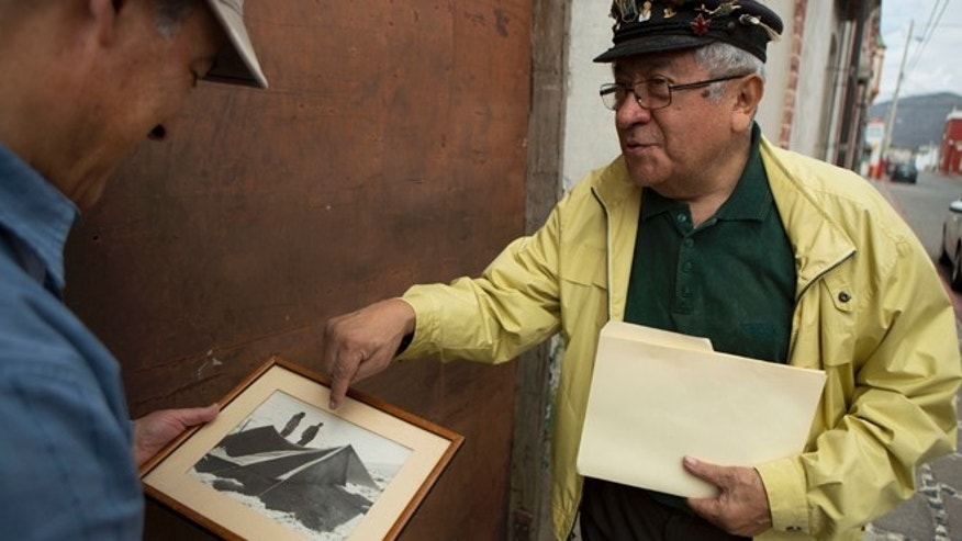 Mountaineer Luis Espinosa shows Gerardo Reyes a photo of an old expedition in Puebla, Mexico, March 10, 2015.