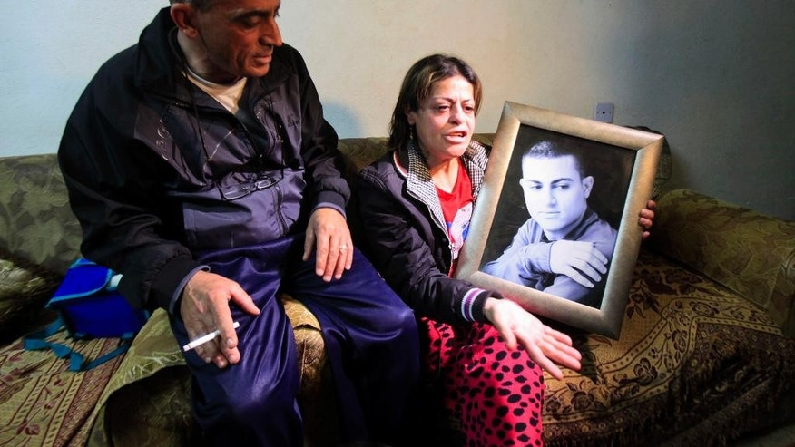 March 10, 2015: Hind, the mother of Muhammad Said Ismail Musallam, holds a picture of her son as she speaks to the Associated Press while seated next to her husband Said Musallam at their home.
