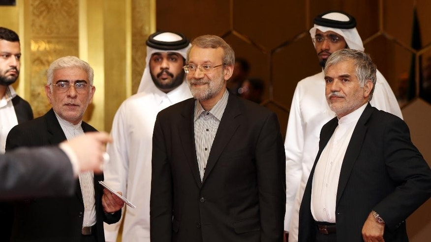 Iranian Parliament Speaker Ali Larijani, center, arrives to address a press conference in Doha, Qatar, Wednesday, March 11, 2015. Larijani said that if it wasn't for Iran's assistance to the Iraqi people and government in confronting the extremist Islamic State group, more countries would be exposed to terrorism. (AP Photo/Osama Faisal)