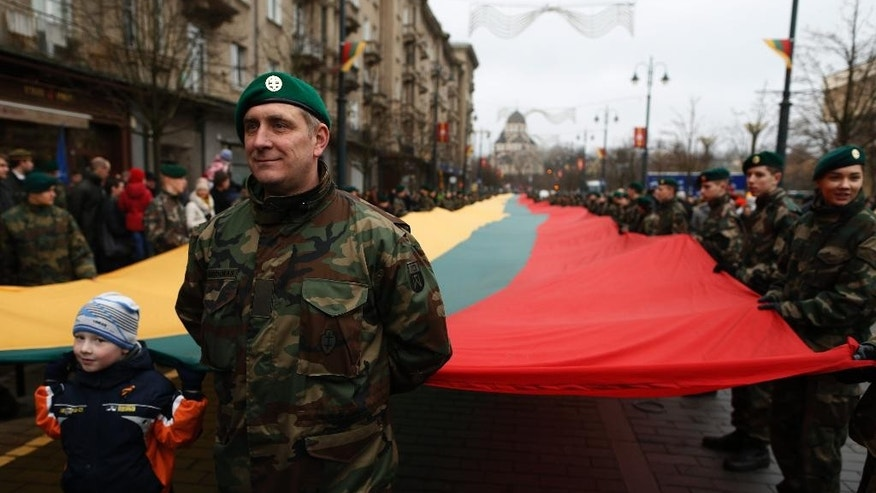 Lithuanian soldiers carry a giant Lithuanian flag during a celebration of Lithuania's independence in Vilnius, Lithuania, Wednesday, March 11, 2015. Lithuania celebrated the 25th anniversary of its declaration of independence from the Soviet Union on Wednesday, recalling the seminal events that set the Baltic nation on a path to freedom and helped lead to the collapse of the U.S.S.R. (AP Photo/Mindaugas Kulbis)