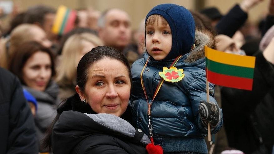 A child holds a flag during a celebration of Independence day at Independence Square, in front of the Parliament Palace in Vilnius, Lithuania, Wednesday, March 11, 2015. Lithuania celebrated the 25th anniversary of its declaration of independence from the Soviet Union on Wednesday, recalling the seminal events that set the Baltic nation on a path to freedom and helped lead to the collapse of the U.S.S.R. (AP Photo/Mindaugas Kulbis)