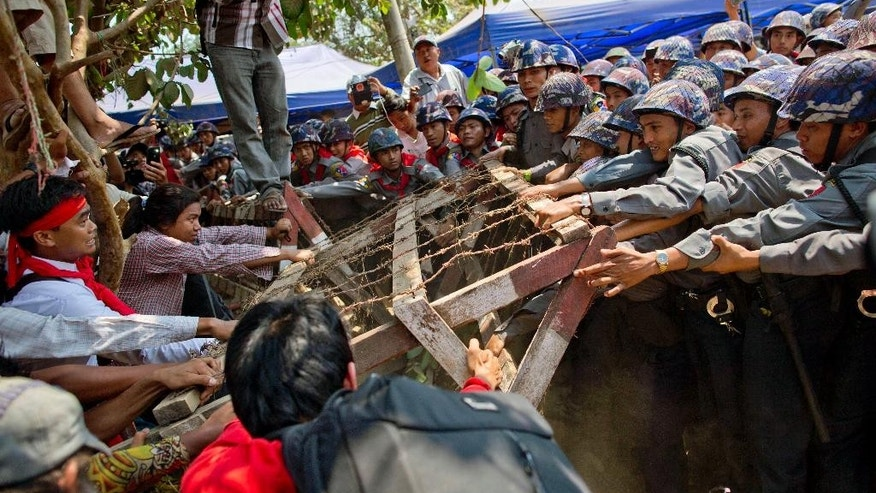 Student protesters struggle with riot police to remove a barricade installed by police during a protest ahead of a crackdown in Letpadan, 140 kilometers (90 miles) north of the country's main city Yangon, Myanmar Tuesday, March 10, 2015. Hundreds of riot police charged at students protesting Myanmar's new education law on Tuesday, pummeling them with batons and then dragging them into trucks, bringing a quick, harsh end to a weeklong standoff. (AP Photo/Gemunu Amarasinghe)