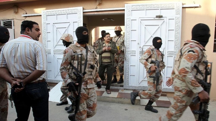Pakistani paramilitary troops raid the Muttahida Quami Movement's offices in Karachi, Pakistan, Wednesday, March 11, 2015. A Pakistani army officer says about 20 suspects were arrested, weapons seized and the premises were sealed during a raid on the headquarters of the well-known political party. (AP Photo/Fareed Khan)