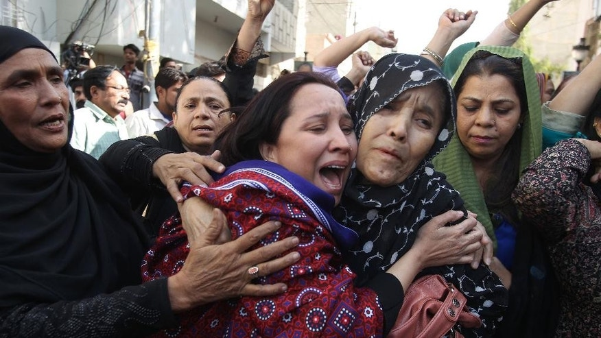 Pakistani women react to the arrest of their family members during a raid at the offices of the Muttahida Quami Movement in Karachi, Pakistan, Wednesday, March 11, 2015. A Pakistani army officer says soldiers raided the headquarters of a well-known political party in Karachi, arresting about 20 suspects, seizing weapons and sealing the premises. (AP Photo/Fareed Khan)