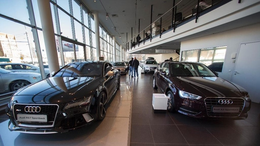 In this photo taken on Tuesday, March  10, 2015, customers walk between cars on a display at an automobile dealership in Moscow, Russia. Russian car sales dropped 37.9 percent year-on-year in February, according to data released Tuesday by the Moscow-based Association of European Businesses, a sharp contrast to steady rises in Europe overall. (AP Photo/Alexander Zemlianichenko)