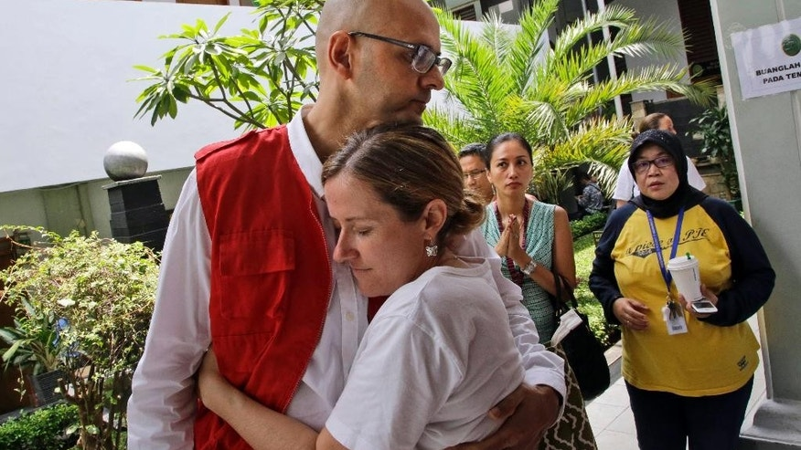 Canadian teacher Neil Bantleman, left, is hugged by his wife Tracy prior to the start of his trial hearing to listen to the prosecutor's demand at South Jakarta District Court in Jakarta, Indonesia, Thursday, March 12, 2015. Bantleman and Indonesian teaching assistant Ferdinant Tjiong were on trial on accusation of sexually abusing a kindergartner on the campus of a prestigious international school in the capital. (AP Photo/Dita Alangkara)