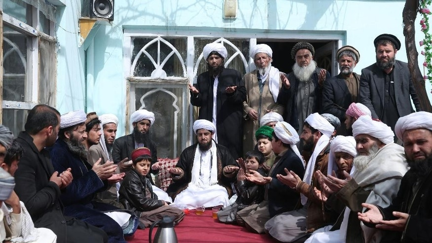 Abdul Waheed Bahaduri, center, a leader of Sufi Muslims, prays in a mosque in Kabul, Afghanistan, Thursday, March 12, 2015. Bahaduri says he has yet to hear from Afghanistan's president following the murder last weekend of his father, brother and nine other Sufi worshippers who were shot dead while they prayed. (AP Photo/Massoud Hossaini)
