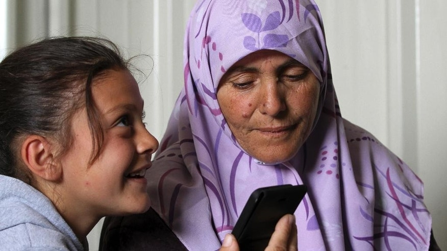 In this photo taken Tuesday, March 10, 2015, Rukaya Bakkar, 7, sitting next to her mother Hamida, 43, talks with her father on the phone at Azraq refugee camp in Azraq, 100 kilometers (62 miles) east of Amman, Jordan. Rukaya's father Mohammed Bakkar lives with his father and son in Lebanon's school-turned refugee shelter, waiting for a day when they can reunite. (AP Photo/Raad Adayleh)