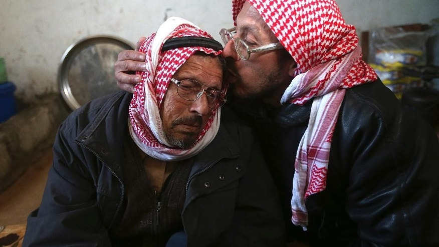 In this photo taken Friday, March 6, 2015, Syrian refugee man Mohammed Bakkar, 44, right, comforts his father Ahmad, 80, as he cries while telling his family separation story during an interview with The Associated Press at a school-turned refugee shelter at the Lebanese-Syrian border village of al-Rama, north Lebanon. For more than two years, they have been waiting for a day when they can reunite with their loved ones living in a Jordan refugee camp. (AP Photo/Hussein Malla)