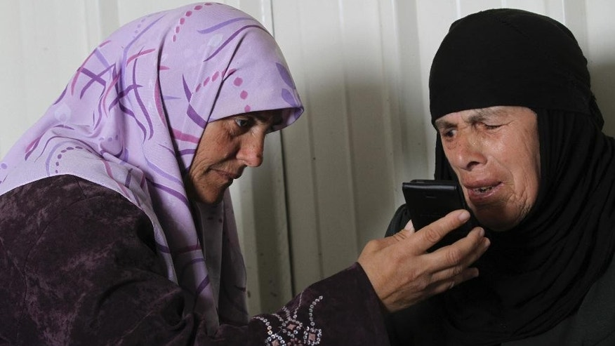 In this photo taken Tuesday, March 10, 2015, Hamida Bakkar, 43, holds a phone for her mother-in-law Fatima Bakkar, 83, as she talks with her husband at Azraq refugee camp in Azraq, 100 kilometers (62 miles) east of Amman, Jordan. Fatima's and Hamida's husbands Ahmad and Mohammed Bakkar, respectively, live in Lebanon's school-turned refugee shelter. They have been separated for more than two years. (AP Photo/Raad Adayleh)