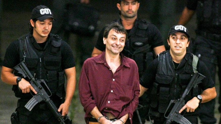 FILE  - This March 19, 2007 file photo, shows Italian leftist fugitive activist Cesare Battisti, center, as he is escorted by Federal Police officers upon his arrival at Brasilia's airport. Brazil's federal police announced Thursday, March 12, 2015, tha they have arrested the former Italian militant Cesare Battisti on a judge's order. The arrest on Thursday of Battisti, who is now being held in Sao Paulo, comes despite his being granted asylum in 2010 by former President Luiz Inacio Lula da Silva and having the Supreme Court approve that asylum in 2013. Battisti had been convicted in Italy for four murders (AP Photo/Eraldo Peres, File)
