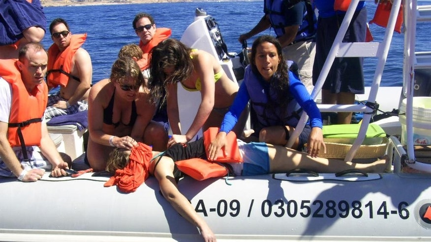 In this photo provided by the Procuraduria Federal de Proteccion al Ambiente (PROFEPA), shows a woman receiving CPR aboard a small boat after she was injured by a breaching grey whale that hit the boat, near the beach resort of Cabo San Lucas, Mexico, Thursday, March 12, 2015. Mexican authorities said that a 35-year-old Canadian woman has died and two other tourists were injured near the beach resort when a surfacing grey whale crashed onto their boat as they came back from a snorkel tour. Mexican navy personnel moved the 35-year-old Canadian to shore and then was taken to a clinic, where she died during treatment. (AP Photo/PROFEPA)