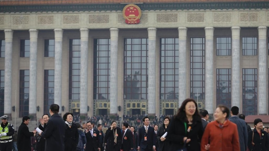 Delegates leave the Great Hall of the People after attending a plenary session of the National People's Congress in Beijing Thursday, March 12, 2015. Thousands of delegates from across the country are in the Chinese capital to attend the annual National People's Congress and the Chinese People's Political Consultative Conference. (AP Photo/Andy Wong)