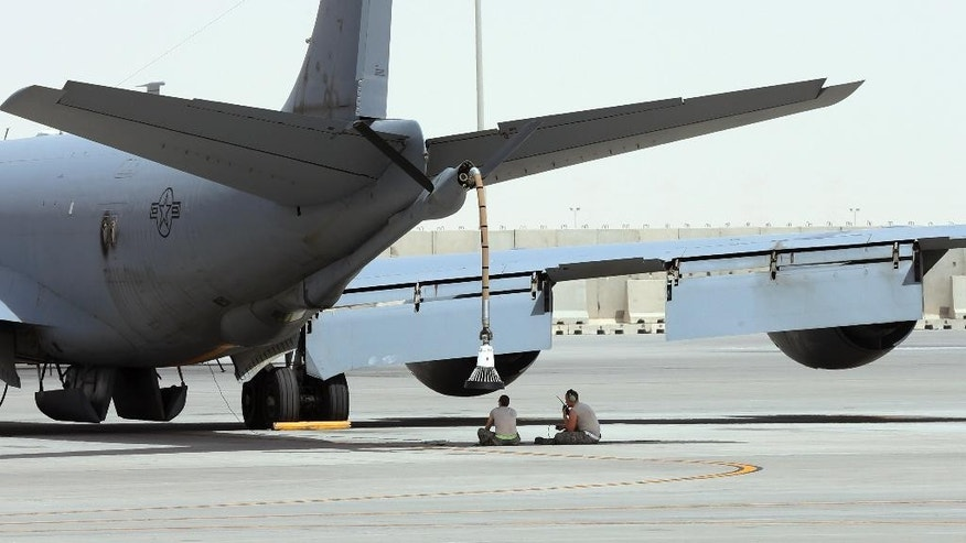 In this photo taken Monday, March 9, 2015, U.S. technicians sit under the KC-135 refueling aircraft at the al-Udeid Air Base in Doha, Qatar. The base is the regional nerve center for the air war against the militants who have taken over nearly a third of Iraq and Syria. That makes it the main hub for coordinating warplanes from the U.S. and 11 other nations in the coalition carrying out bombing raids. (AP Photo/Osama Faisal)