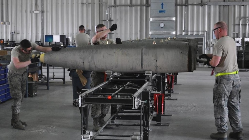 In this photo taken Tuesday, March 10, 2015, members of a U.S. Air Force munitions team assemble guided bombs to support the 379th Air Expeditionary Wing at the al-Udeid Air Base in Qatar. The base is the regional nerve center for the air war against the militants who have taken over nearly a third of Iraq and Syria. That makes it the main hub for coordinating warplanes from the U.S. and 11 other nations in the coalition carrying out bombing raids. (AP Photo/Adam Schreck)