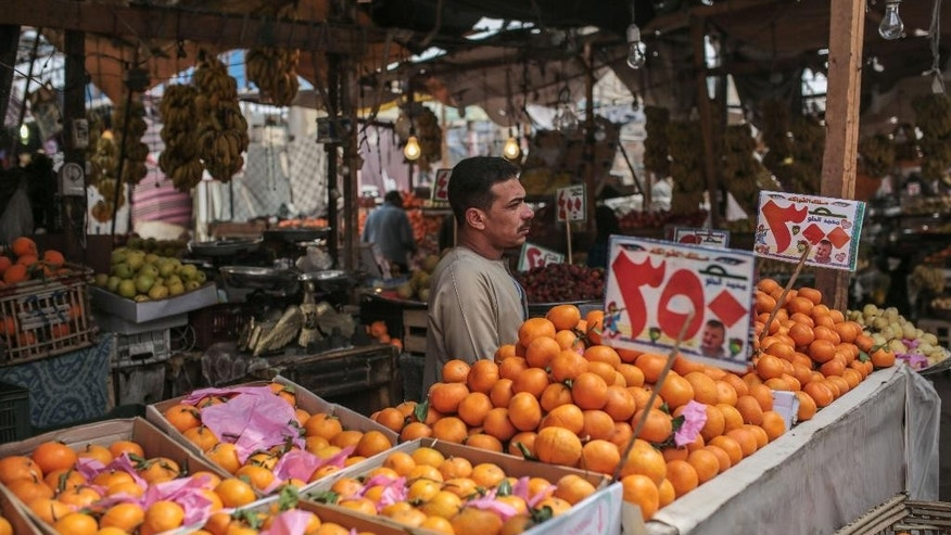 In this Monday, March 9, 2015 photo, a fruit vendor waits at a local market in Sixth of October city, a suburb southwest of Cairo, Egypt. Egypt is set to hold a major economic conference to attract foreign investors starting on Friday. The government says new investment is crucial to rescue an economy gutted buy four years of turmoil since Egypt's 2011 uprising. (AP Photo/Mosa'ab Elshamy)