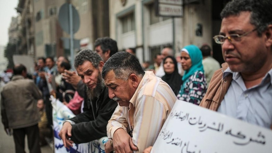 In this Monday, March 9, 2015 photo, workers protest withheld wages in downtown Cairo, Egypt. Just days before Egypt holds a major economic conference to attract foreign investors, scores of workers held the latest in a string of protests outside government offices in Cairo, complaining that officials are siding with investors running their company who have not paid them for months.(AP Photo/Mosa'ab Elshamy)