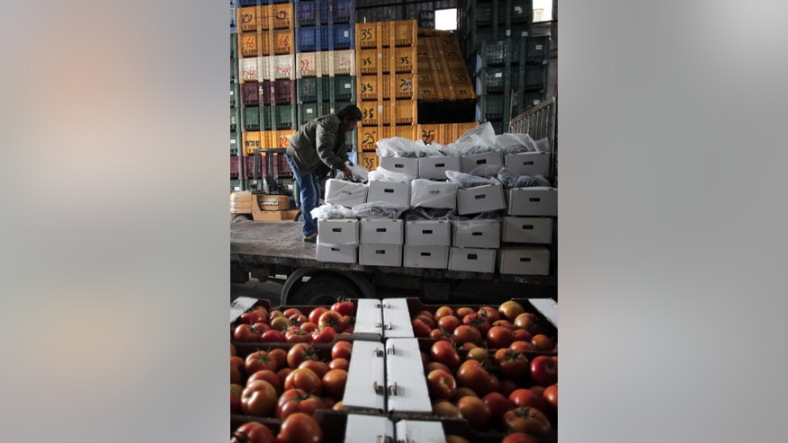In this Wednesday, March 11, 2015 photo, Palestinian workers load boxes with eggplants and tomatoes to export them to Israel, in the town of Deir el-Balah, central Gaza Strip. Israel on Thursday began importing Gaza's agricultural produce for the first time in about eight years, partly easing one of many restrictions imposed on the Palestinian territory since Islamic Hamas militant group seized it in 2007. (AP Photo/Khalil Hamra)