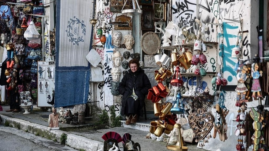 A woman sits at the entrance of a souvenir shop at Monastiraki tourist district in Athens, on Thursday, March 12, 2015. Talks between Greece and its creditors began in Brussels on Wednesday to cement a series of reforms Athens must implement in order to get the remaining bailout funds released and avoid bankruptcy. (AP Photo/Yorgos Karahalis)