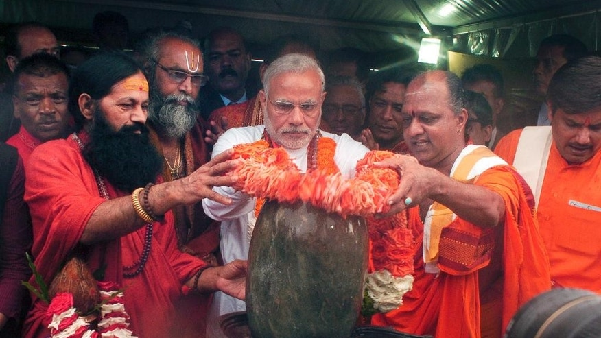 India's Prime Minister Narendra Modi, center, places flowers on a lingam or shivling, a representation of the Hindu deity Shiva used for worship, during a Hindu religious ceremony at the crater lake of Grand Bassin (also known as Ganga Talao), during the second day of his visit to the Republic of Mauritius Thursday, March 12, 2015. According to the Indian Prime Minister's website Modi is leading a delegation on a three nation tour of Seychelles, Mauritius and Sri Lanka to strengthen ties between the countries. (AP Photo/George Michel)