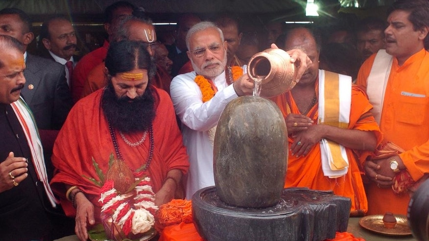 India's Prime Minister Narendra Modi, center, pours holy water on a lingam or shivling, a representation of the Hindu deity Shiva used for worship, during a Hindu religious ceremony at the crater lake of Grand Bassin (also known as Ganga Talao), during the second day of his visit to the Republic of Mauritius Thursday, March 12, 2015. According to the Indian Prime Minister's website Modi is leading a delegation on a three nation tour of Seychelles, Mauritius and Sri Lanka to strengthen ties between the countries. (AP Photo/George Michel)