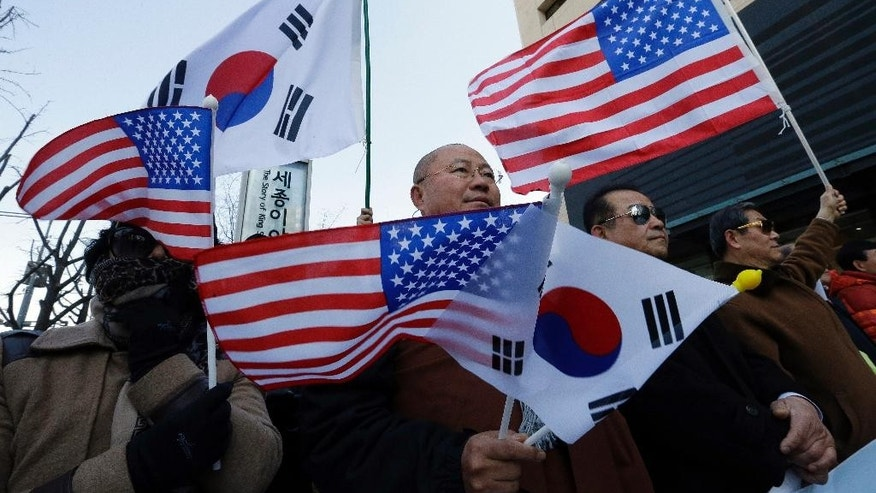 South Korean conservative activists with the flags of South Korean and the United States stage a rally denouncing the attack on U.S. Ambassador to South Korea Mark Lippert and demanding the alliance between South Korea and the United States, near the U.S. Embassy in Seoul, South Korea, Friday, March 13, 2015. South Korean police said Friday that an anti-U.S. arrested last week for allegedly stabbing Lippert had intended to kill the envoy to highlight his protest against ongoing U.S.-South Korean military drills. (Ahn Young-joon)